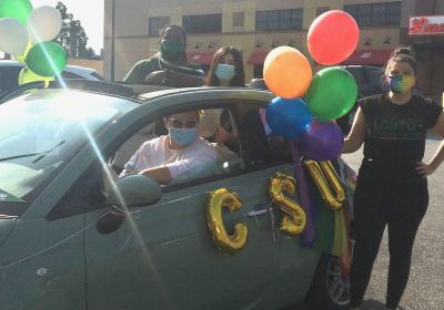 A CSU student standing by one of the cars in the CLE Pride Ride.
