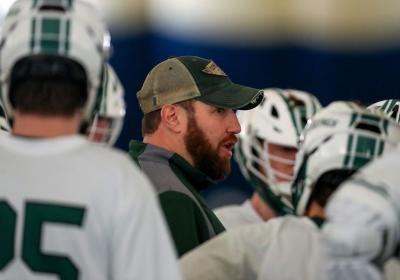CSU Lacrosse coach Andy German inside the huddle with his team.